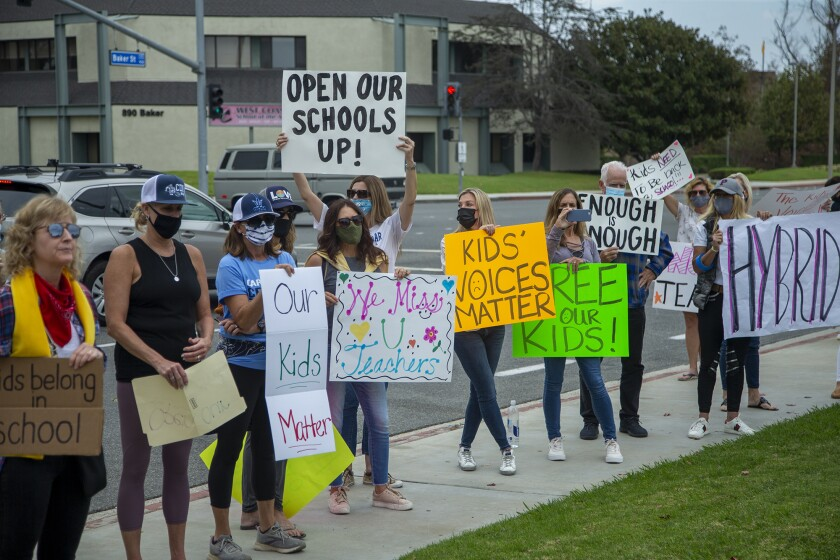 Students and parents protest outside the Newport-Mesa Unified School District office on Oct. 23.