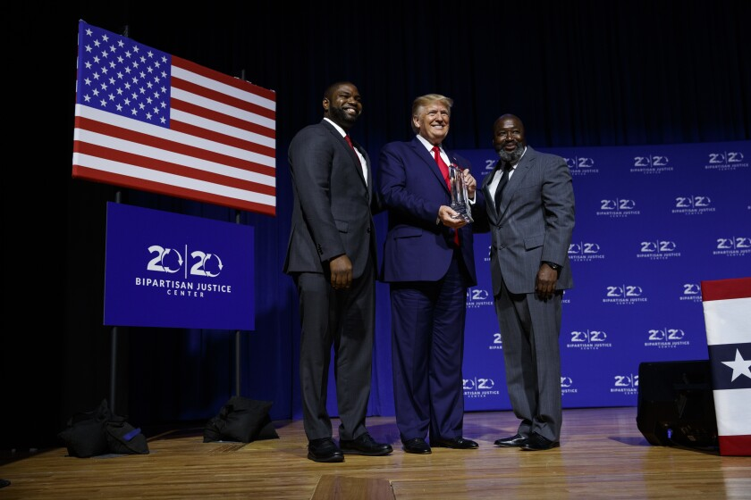 President Trump is awarded the Bipartisan Justice Award by Matthew Charles, right, one of the first prisoners released under the First Step Act, during a forum Friday at Benedict College in Columbia, S.C.