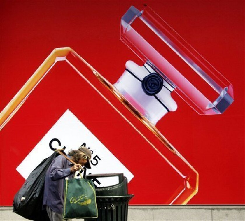 In this Sept. 3, 2008 file photo, a scavenger looks for plastic bottles from a public trash bin in front of a promotion of a perfume in Shanghai, China. The politically divisive income gap between China's affluent city-dwellers and its huge farm population expanded to its widest level ever last y