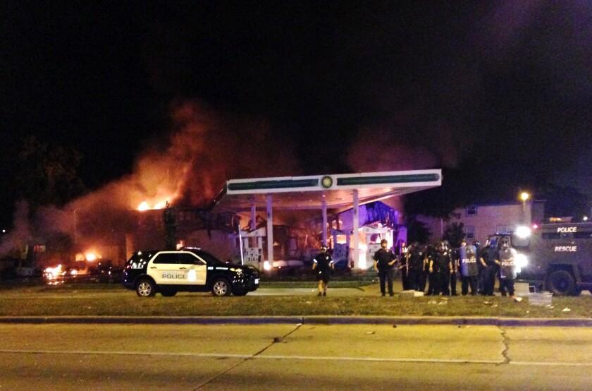 Autoridades responden a un incendio cerca en una gasolinera mientras docenas de personas protestan por la muerte de un hombre por disparos de la policía en Milwaukee, Wisconsin, el 13 de agosto de 2016. (AP Foto/Gretchen Ehlke)