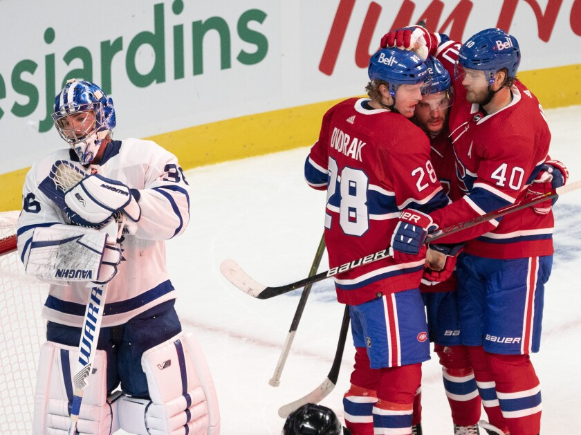Montreal Canadiens' Christian Dvorak (28) celebrates with teammates Jonathan Drouin (92) and Joel Armia (40) after scoring the second goal against Toronto Maple Leafs goaltender Jack Campbell (36) during first-period preseason NHL hockey game action in Montreal, Monday, Sept. 27, 2021. (Ryan Remiorz/The Canadian Press via AP)