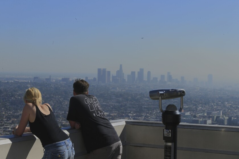 Visitors to the Griffith Observatory take in a smoggy view of the L.A. Basin. More than 7 million Californians live in highly polluted and socioeconomically vulnerable areas, which put them at higher risk for cancer, asthma, low-birth weights and other negative health effects, according to state research.