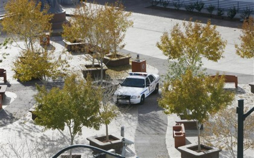 A court marshal vehicle patrols the 5th Street School courtyard across the street from the Lloyd D. George federal courthouse building in downtown Las Vegas following an officer involved shooting Monday, Jan. 4, 2010 in Las Vegas. A court security officer and the suspect were killed. (AP Photo/Isaac Brekken)