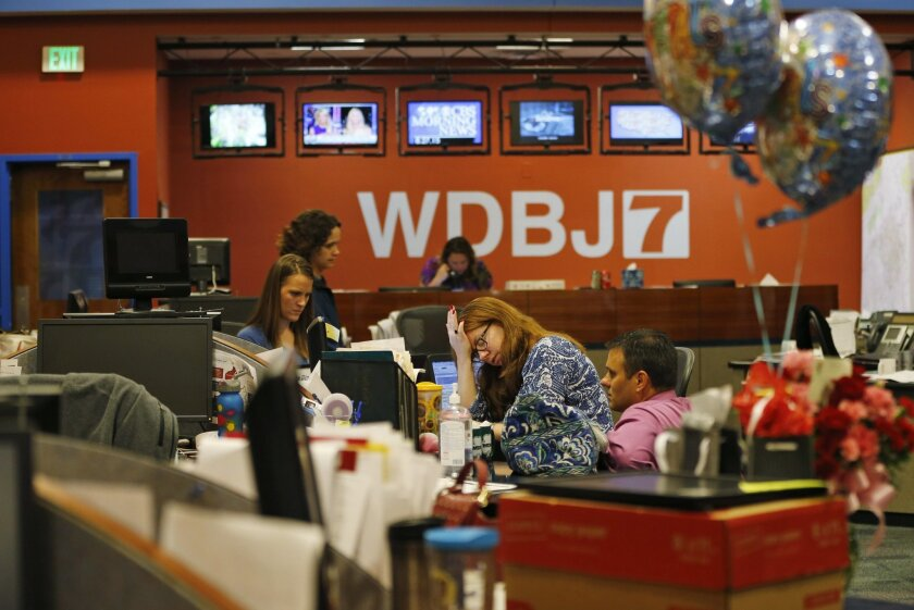 Members of the WDBJ-TV7 news staff prepare for the early morning newscast at the station, Thursday, Aug. 27, 2015, in Roanoke, Va. Reporter Alison Parker and cameraman Adam Ward were killed by a former colleague during a live broadcast Wednesday, while on assignment in Moneta. The balloons and flowers, at right, are addressed to Ward's fiancee, Melissa Ott, who was celebrating her last day at WDBJ on Wednesday, before moving to a station in North Carolina. (AP Photo/Steve Helber)