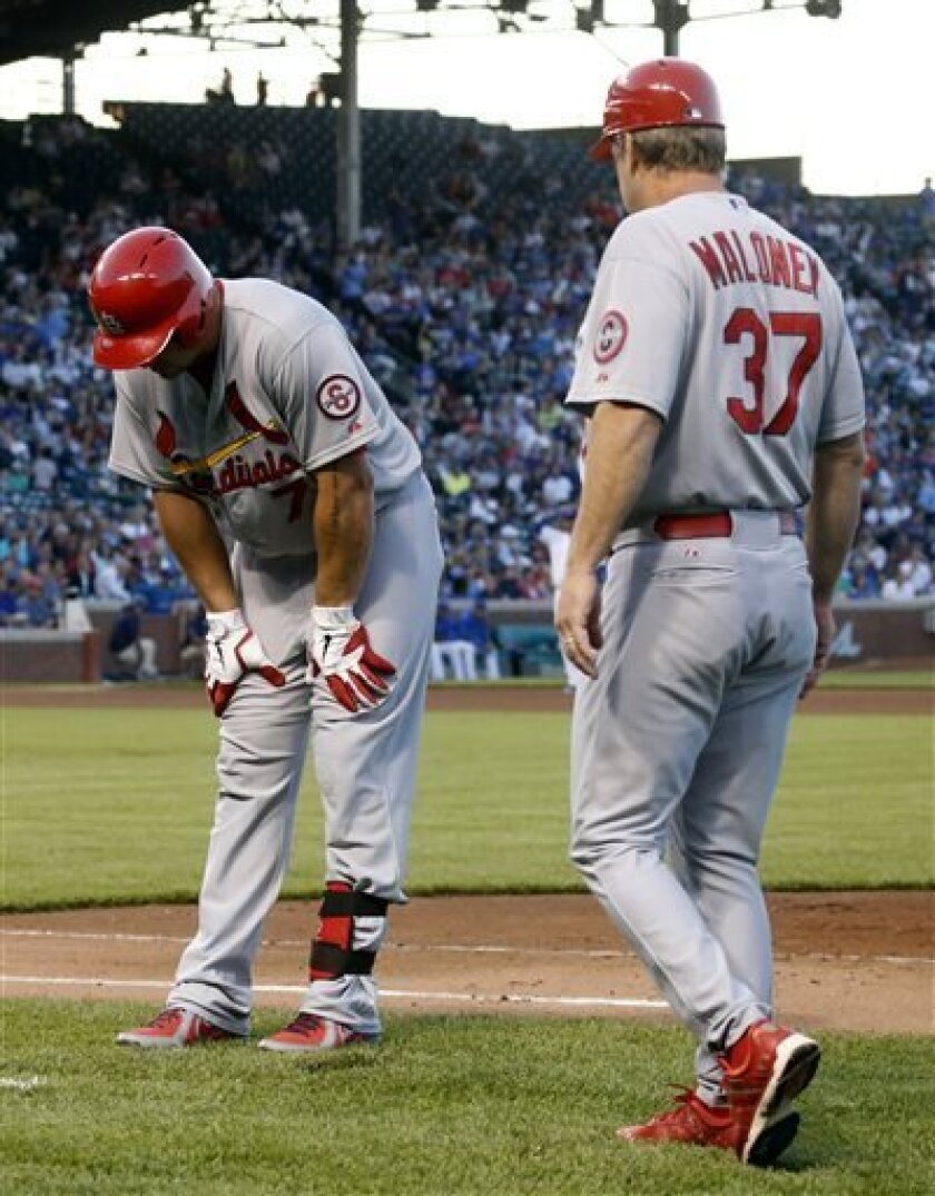 St. Louis Cardinals' Matt Holliday, left, pulls up short of first base after hitting a ground ball to Chicago Cubs second baseman Darwin Barney during the fourth inning of a baseball game on Thursday, July 11, 2013, in Chicago. First base coach Chris Maloney walks up to Holliday. (AP Photo/Charles Rex Arbogast)