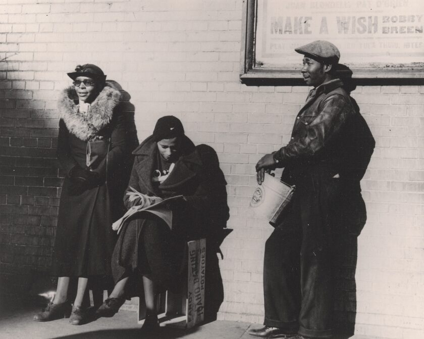 A vintage black and white image show two Black women and one Black man in the sunshine before a brick wall.