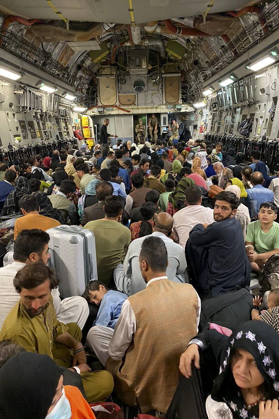Afghan people sit inside a U S military aircraft to leave Afghanistan, at the military airport in Kabul.