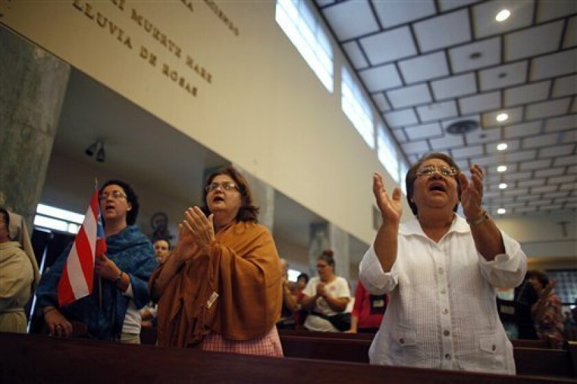 People attend a Mass in honor of Puerto Rico's Archbishop Roberto Gonzalez Nieves at a church in San Juan, Puerto Rico, Wednesday, May 8, 2013. Roman Catholics in Puerto Rico rallied Wednesday around the archbishop who is apparently under pressure from the Vatican to resign for allegedly covering u