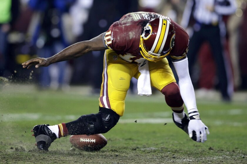 FILE - This Jan. 6, 2013 file photo shows Washington Redskins quarterback Robert Griffin III twisting his knee as he reaches for the loose ball after a low snap during the second half of an NFL wild card playoff football game against the Seattle Seahawks in Landover, Md. (AP Photo/Matt Slocum, File)