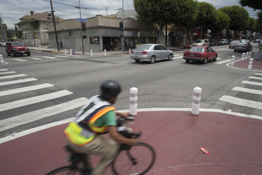 A cyclist rounds the corner where the curbs have been extended and white pylons mark areas designated with red paint to help slow traffic at the intersection of Cesar Chavez Boulevard and St. Louis Street in Los Angeles.