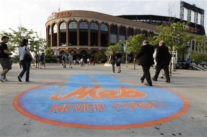 Fans pass a chalk drawing in memory of the Sept. 11, terrorist attacks as they approach Citi Field before a baseball game between the New York Mets and the Washington Nationals, Wednesday, Sept. 11, 2013, in New York. (AP Photo/Frank Franklin II)