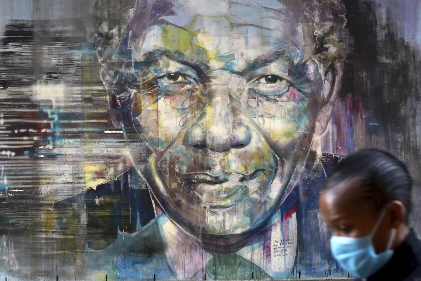 A woman walks past a mural of Nelson Mandela in Cape Town, South Africa, on Saturday, which is International Mandela Day.