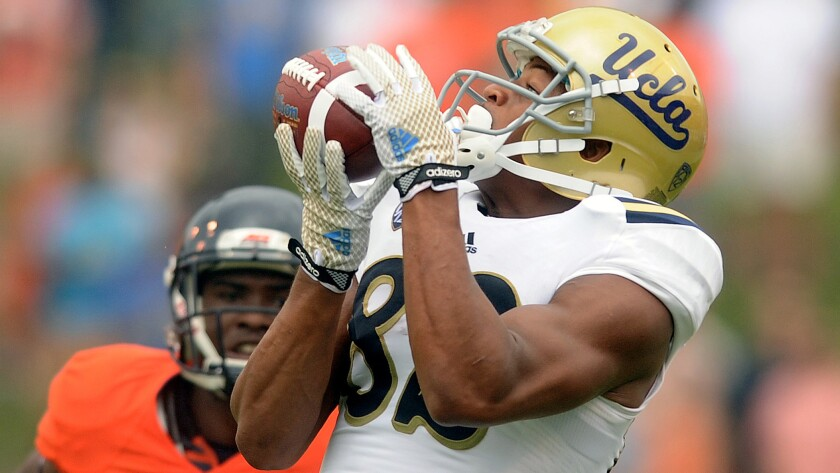 UCLA wide receiver Eldridge Massington hauls in a long pass during the Bruins' win over Virginia on Aug. 30.