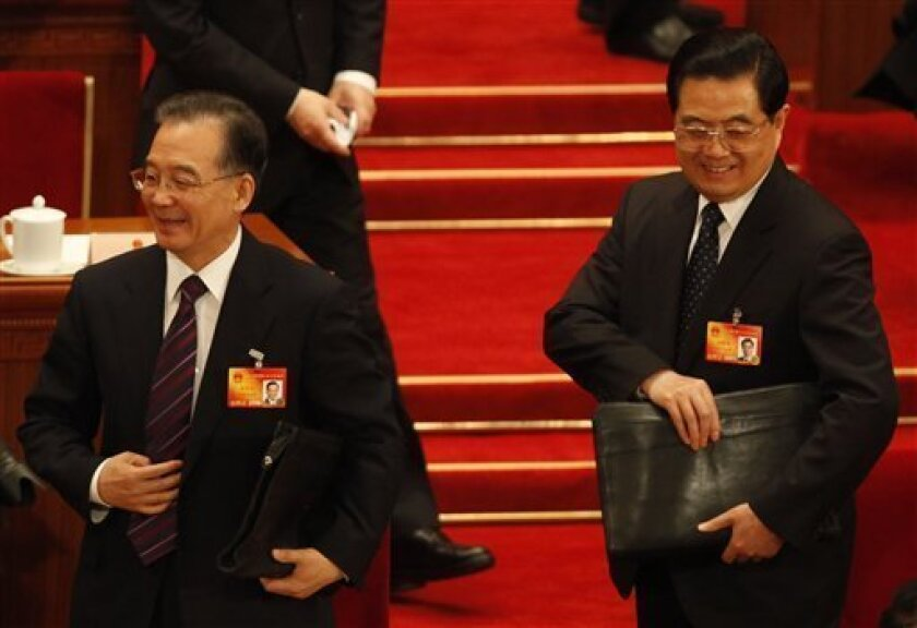 Chinese Premier Wen Jiabao, left, and President Hu Jintao prepare to leave after a session of the annual National People's Congress at Beijing's Great Hall of the People, Monday, March 8, 2010. (AP Photo/Gemunu Amarasinghe)