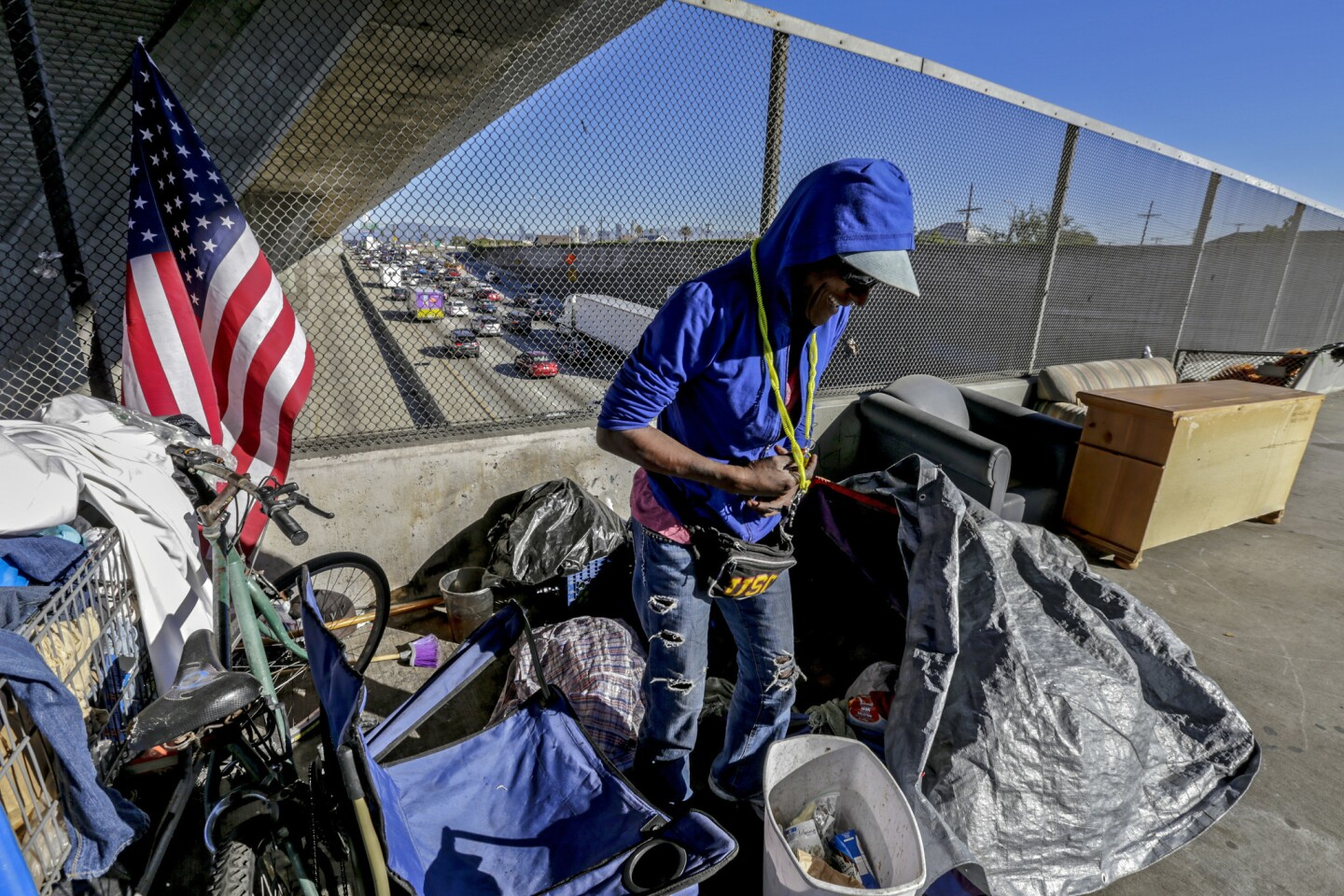 Alice Myles, 60, who is homeless, steps out of her tent pitched over 42nd. Street bridge over 110 Freeway in Los Angles.