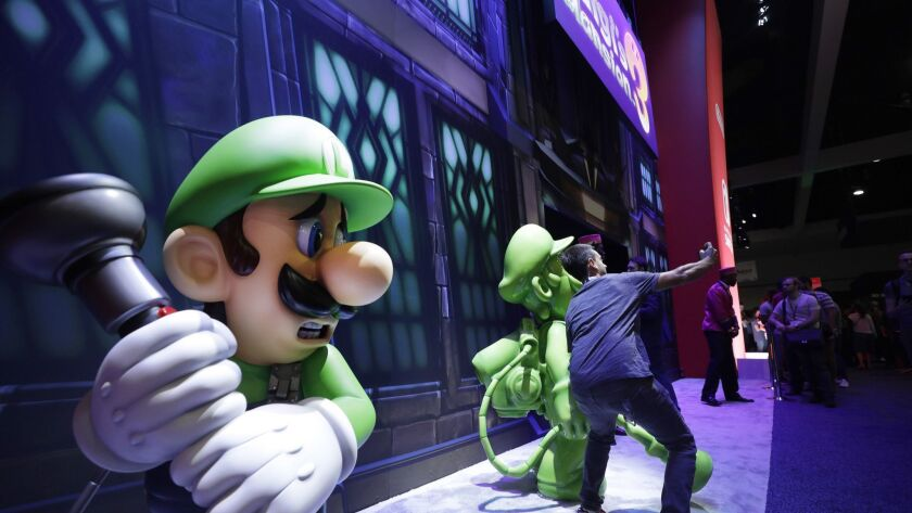 """An attendee takes a picture in front of """"Luigi's Mansion 3"""" during the 2019 E3."""