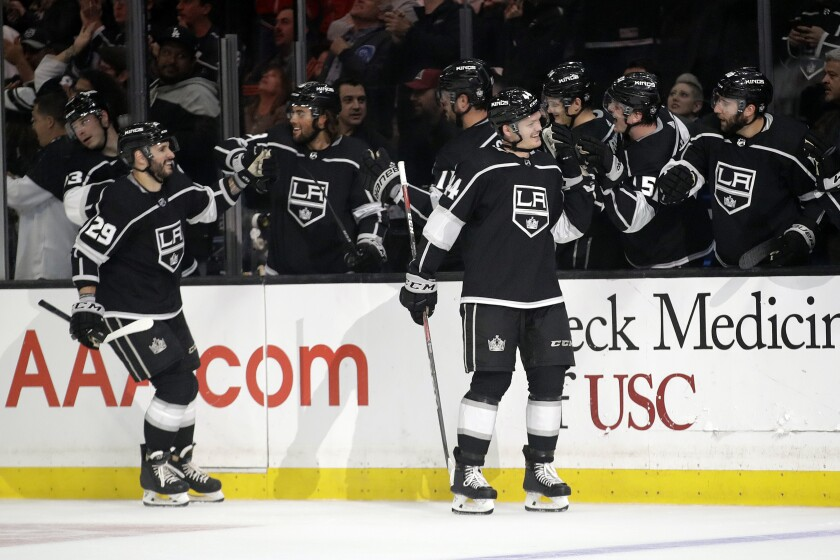 Kings' Mikey Anderson, right, celebrates his goal with teammates during the first period against the Colorado Avalanche on Monday at Staples Center.