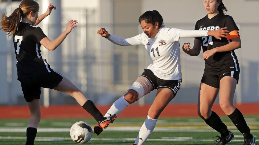 Los Amigos High's Vidalia Abarca (11) battles against South Pasadena's Emily Dunn (7) and Riley Sega