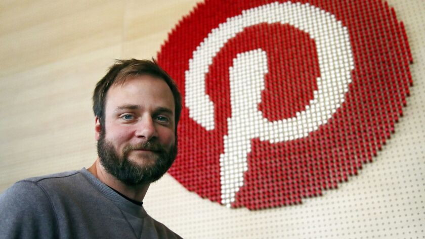 Evan Sharp, Pinterest co-founder and chief product officer, poses beside a wall of pegs symbolizing the company logo at its headquarters in San Francisco.