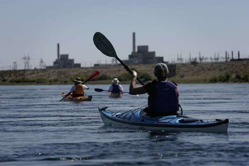 Kayakers paddle the Columbia River near the nuclear reactor that was a home to the Manhattan Project. The river is under threat from radioactive waste leaks.