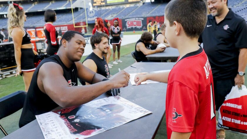 San Diego State's Ryan Pope gives fist pump to fan Brody Mongold, 9, during an autograph session after the team's scrimmage Saturday evening at SDCCU Stadium.