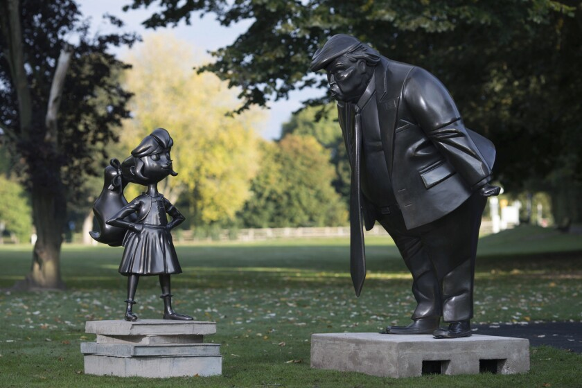 A statue of the Roald Dahl character Matilda next to President Trump, in Great Missenden, Buckinghamshire, England. The two statues show Trump in a face-to-face confrontation with Matilda, whose story was first published 30 years ago.