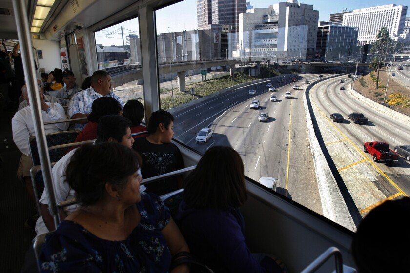 Metro officials say a concrete overpass support will have to be repaired. Above, passengers look over the 101 Freeway on the debut for the Metro Gold Line's east side extension in 2009.