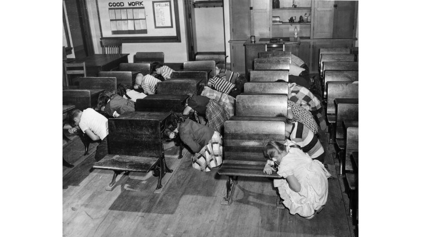 Dec. 1, 1950: Third-graders at Clifford Street School kneel at desks and cover their faces and eyes with their arms during a civil defense drill.