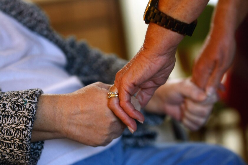 A registered nurse checks the strength of a patient's grip while performing a home visit in Denver, Colo. in 2009.