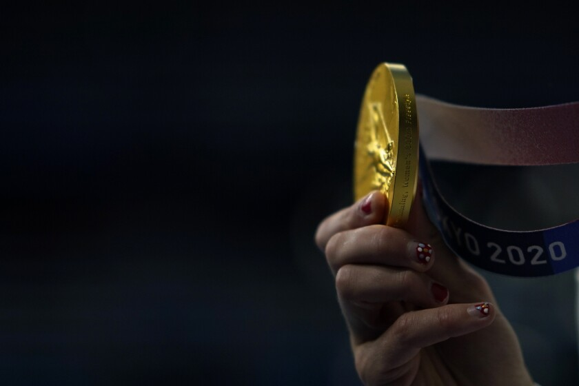 Katie Ledecky, of the United States, shows her gold medal after winning the women's 800-meter freestyle final at the 2020 Summer Olympics, Saturday, July 31, 2021, in Tokyo, Japan. (AP Photo/David Goldman)