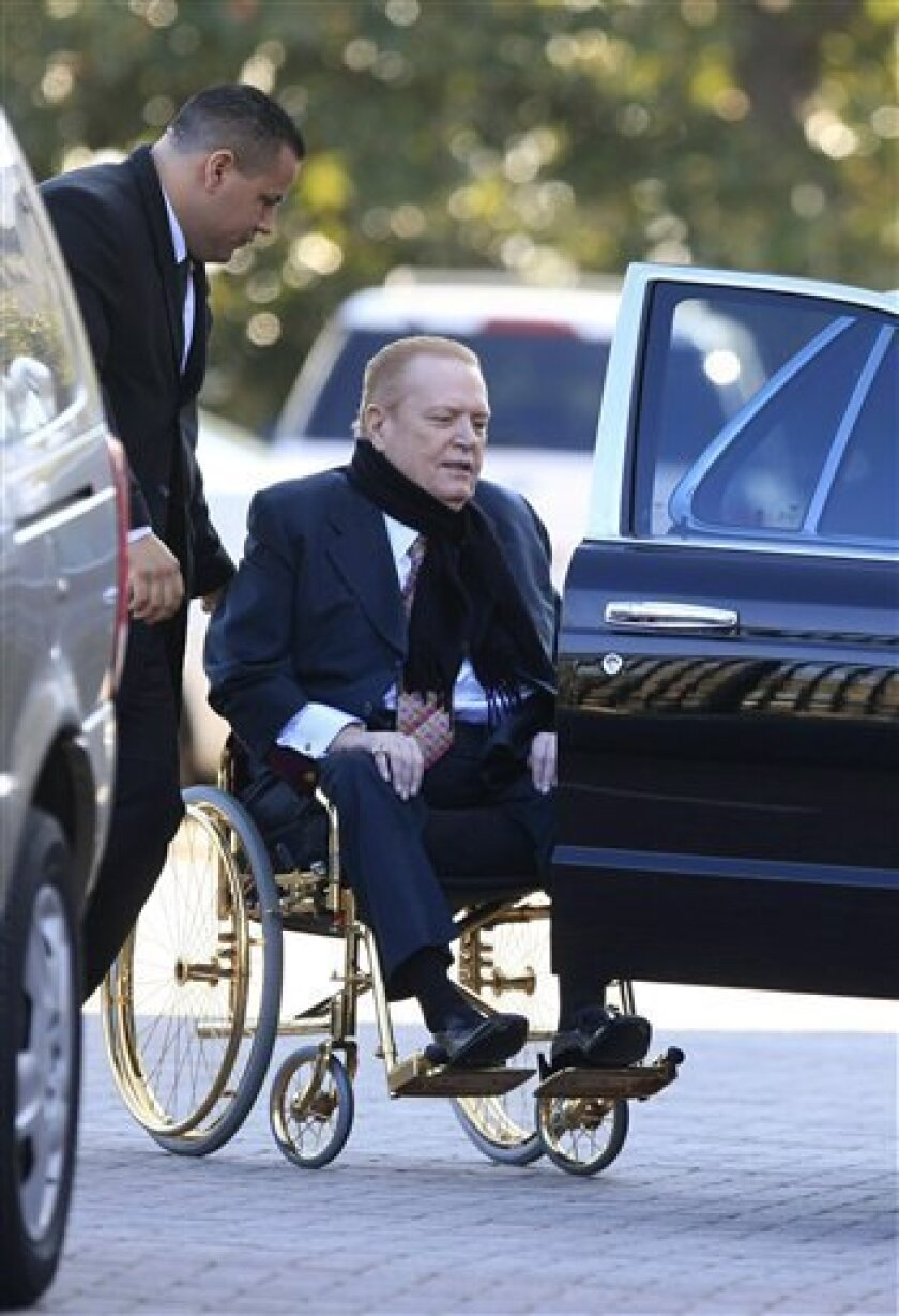 """Hustler publisher Larry Flynt is helped by an unidentified assistant, as he leaves the US District Court in downtown Los Angeles on Wednesday, Dec. 9, 2009. Flynt took the stand Tuesday in the first day of his federal trademark infringement trial against his nephews, Jimmy Jr. and Dustin, who earlier this year launched their own line of adult films under the name """"Flynt."""" Calling their films """"inferior products"""" and """"knock-off goods,"""" the porn mogul promptly sued, accusing them of trying to ride on the coattails of his fame and muddying the quality his customers have come to expect from his products. (AP Photo/Damian Dovarganes)"""