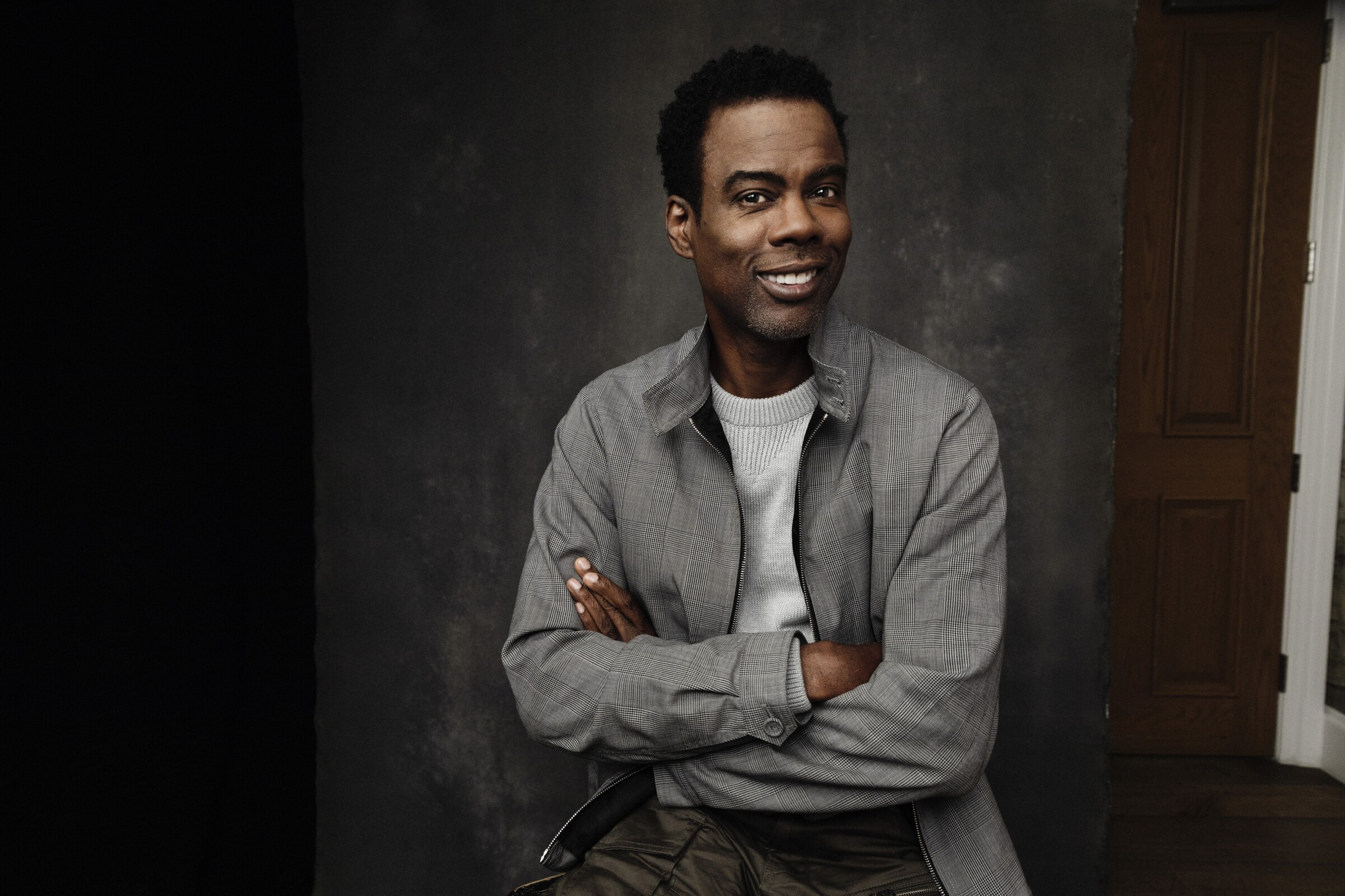 A portrait of Chris Rock, smiling and wearing a jacket with his arms crossed.