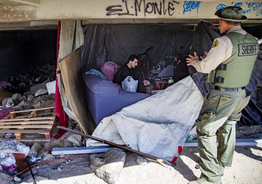 A sheriff's deputy visits a homeless emcampment