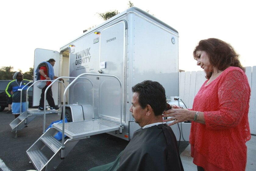 Volunteer hairstylist Martha Alboney gives Jose Escoto a haircut at the Turning the Hearts Center in Chula Vista. A portable shower (background) was also available for homeless living in their cars or on the street.