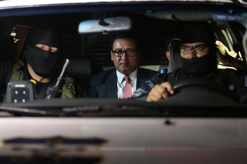 Miembros de la Policía Nacional Civil trasladan al exfical salvadoreño Luis Martínez, quien encabezó la Fiscalía General de la República hasta el pasado mes de enero, y quien fue detenido por los delitos de encubrimiento, fraude procesal y omisión de la investigación en San Salvador (El Salvador).
