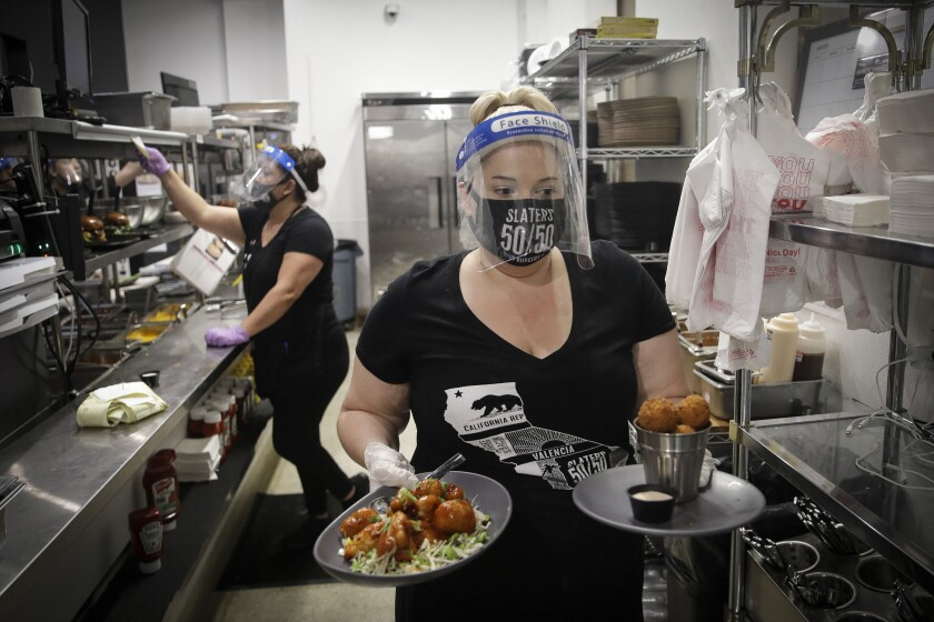 A waitress takes a food order from the kitchen at Slater's 50/50 in Santa Clarita.