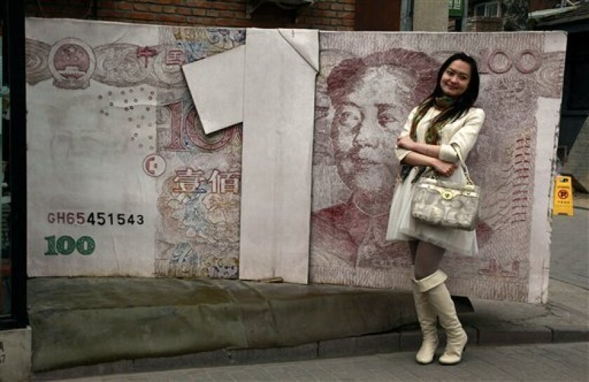In this picture taken on March 15, 2012, a Chinese woman poses for photos near a sculpture depicting a Chinese yuan note at an art district in Beijing, China. Premier Wen Jiabao, China's top economic official, said Tuesday, April 3, 2012, its state-owned banks are monopolies that must be broken up, acknowledging mounting economic and political pressure to reform an industry whose vast profits are fueling public anger. (AP Photo/Ng Han Guan)