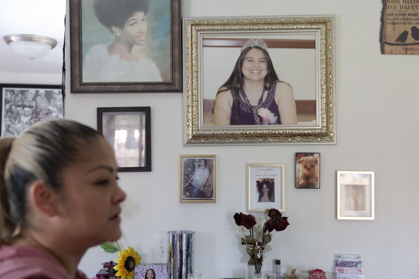 Ena Palma, left, speaks of memories with her sister, Yanet Palma-Perez, who is pictured on the wall in her Wilmington, Calif., home. Yanet Palma-Perez died at the hands of her husband in 2016.