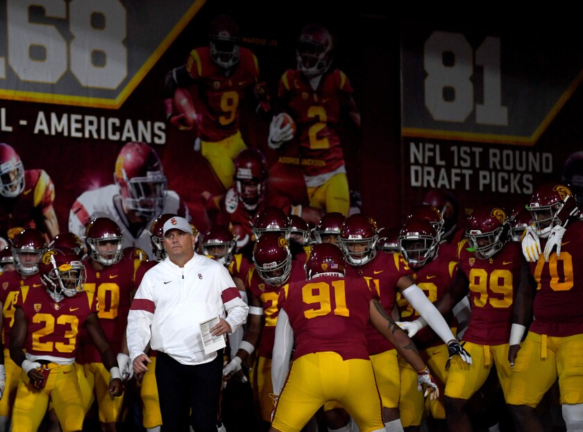 USC coach Clay Helton leads the Trojans onto the field.