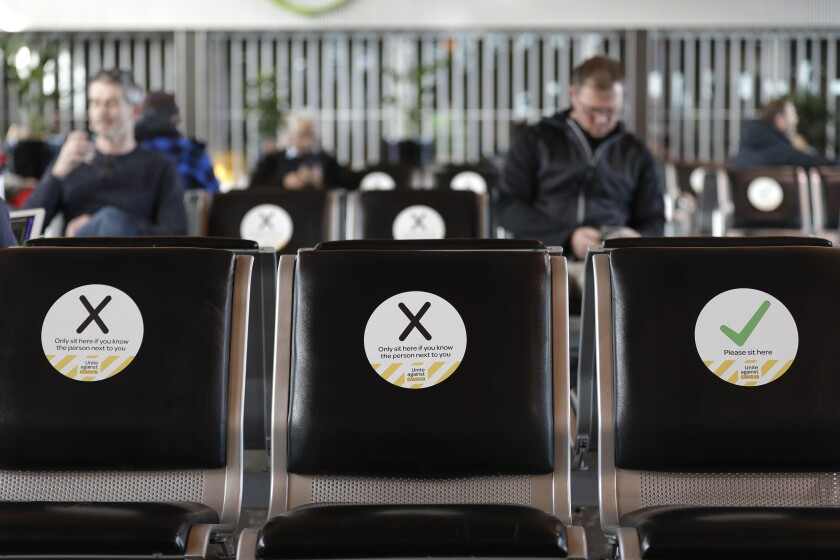 FILE - In this May 14, 2020, file photo, passengers wait to board their flight at Christchurch Airport in Christchurch, New Zealand.New Zealand has eradicated the coronavirus from its shores after health officials reported on Monday June 8, 2020 that the final person known to have contracted an infection had recovered. (AP Photo/Mark Baker, File)