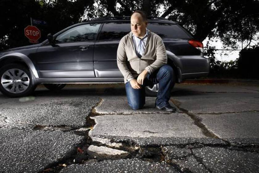 Gregory Leskin at Angus Street and Moreno Drive, near his Silver Lake home; he put in a request for repairs to the buckled and cracked pavement nearly three years ago, and is still waiting.