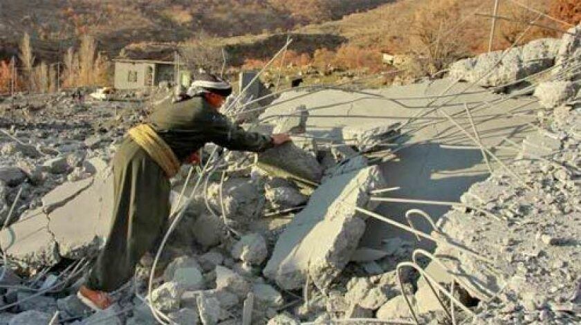 SEARCHING: A villager looks through a rubble at the Qlatooka village near Iraq's border with Turkey.