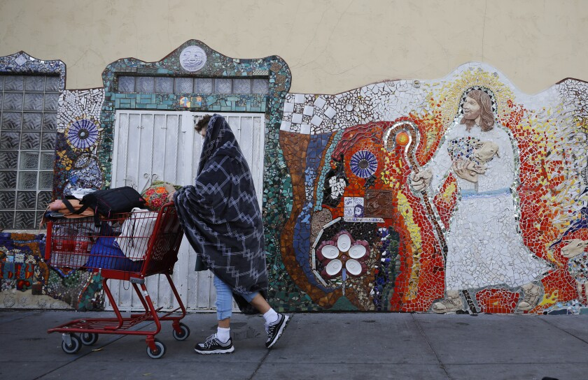 In this photo from March, a homeless man walks by God's Extended Hand Ministries in downtown San Diego.