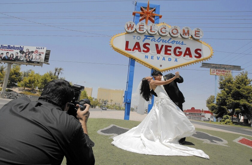 """A couple get married with the """"Welcome to Fabulous Las Vegas"""" sign in the background. The landmark sign's designer, Betty Willis, has died at age 91."""
