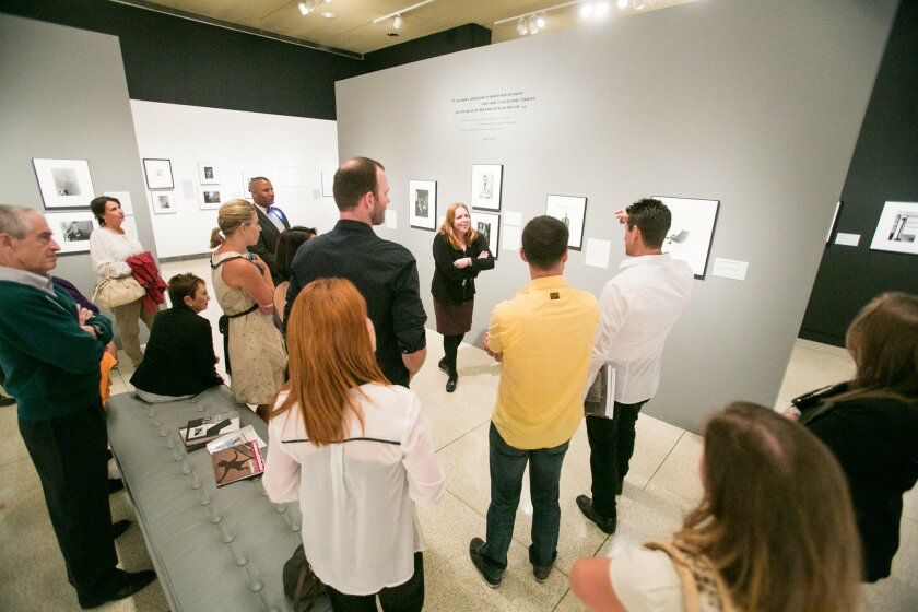 """Amy Galpin talks to visitors at the San Diego Museum of Art's exhibition of """"Masterclass: Arnold Newman"""""""