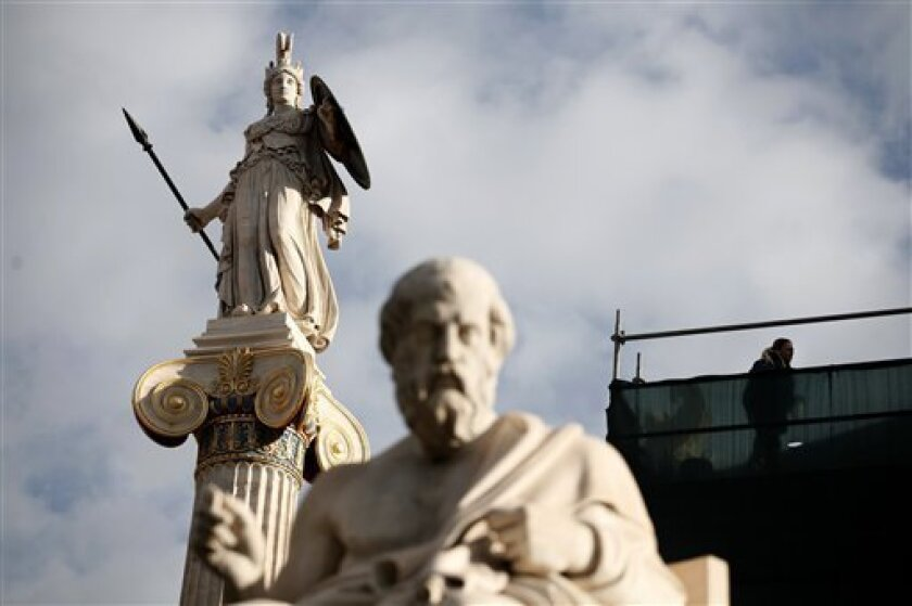 Restoration continues on the Athens Academy building behind 19th century marble statues of ancient Greek philosopher Plato and ancient goddess Athena, left, in central Athens, on Wednesday, Dec. 12, 2012. Greece will buy back Euro 31.9 billion ($41.5 billion) of its bonds from private investors at a third of their nominal price, the debt management agency said Wednesday, lightening its crushing debt load and meeting a key condition to receive vital rescue loans.(AP Photo/Petros Giannakouris)