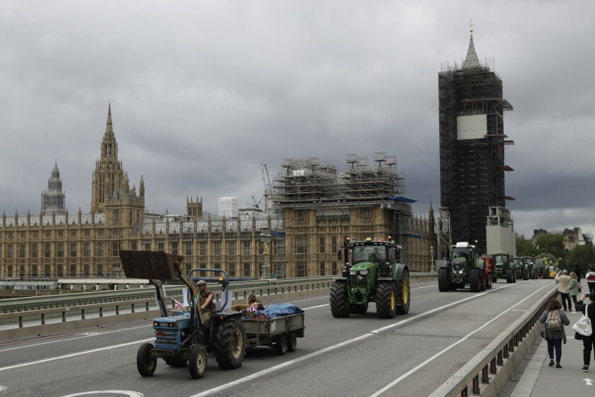 Farmers from the group Save British Farming drive tractors across Westminster Bridge, backdropped by the Houses of Parliament and the scaffolded Big Ben tower in London, in a protest against cheaply produced lower standard food being imported from the U.S. after Brexit that will undercut them, Wednesday, July 8, 2020. (AP Photo/Matt Dunham)