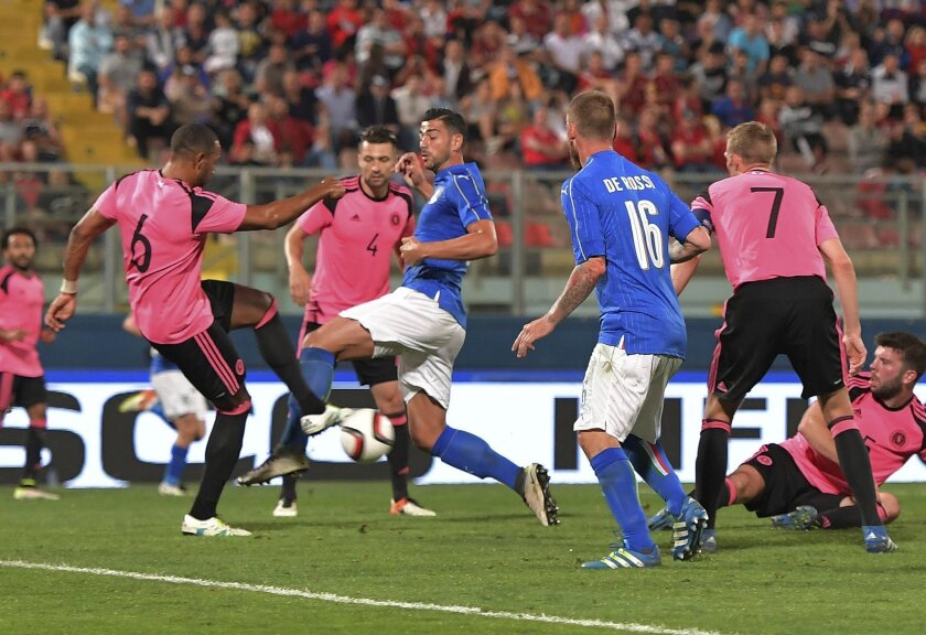 Italy's Graziano Pellè, center, vies for the ball with Scotland's Matt Phillips, left, before scoring during a friendly match between Italy and Scotland, in preparation for the upcoming Euro 2016 European Championships, at the Ta' Qali stadium in Attard, Malta, Sunday, May 29, 2016. (AP Photo/Rene Rossignaud)