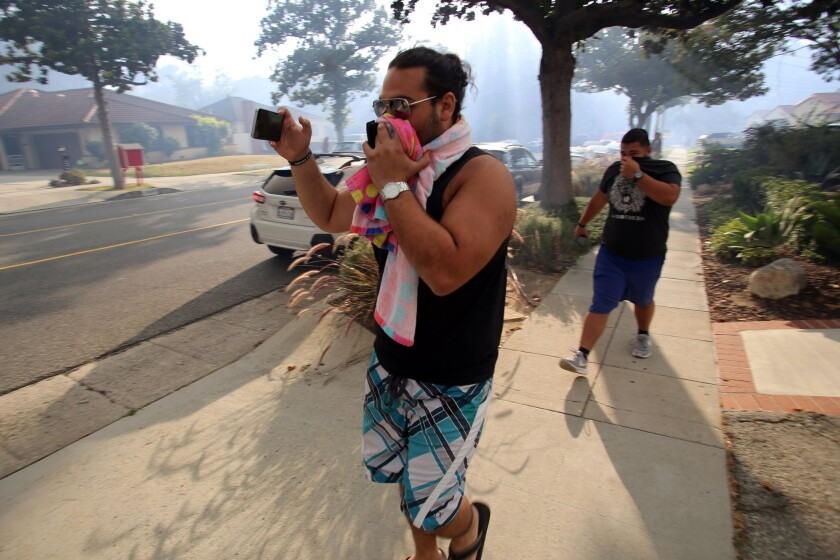 Residents cover their faces as a brush fire burns in the hills in the Glenoaks Canyon area in Glendale.