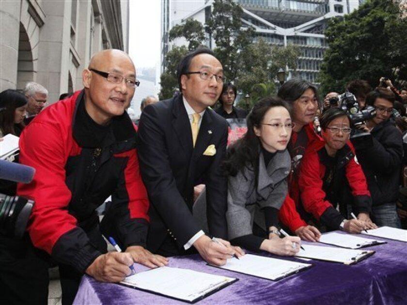 Five Hong Kong legislators, from left, Albert Chan, Alan Leong, Tanya Chan, Leung Kwok-hung and Wong Yuk-man sign the resignation letter outside the Legislative Council in Hong Kong Tuesday, Jan. 26, 2010. The five legislators have resigned to pressure China for democracy in this semiautonomous for